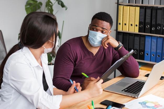 Zwei personen im büro arbeiten während einer pandemie mit medizinischen masken zusammen