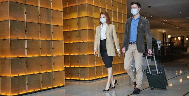 Zwei personen in medizinischen masken, die mit einem rollkoffer in einer hotelhalle spazieren. website-banner