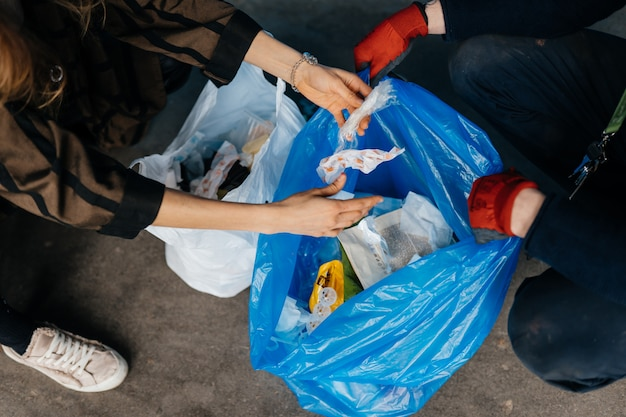 Zwei personen sortieren müll. konzept des recyclings. kein verlust