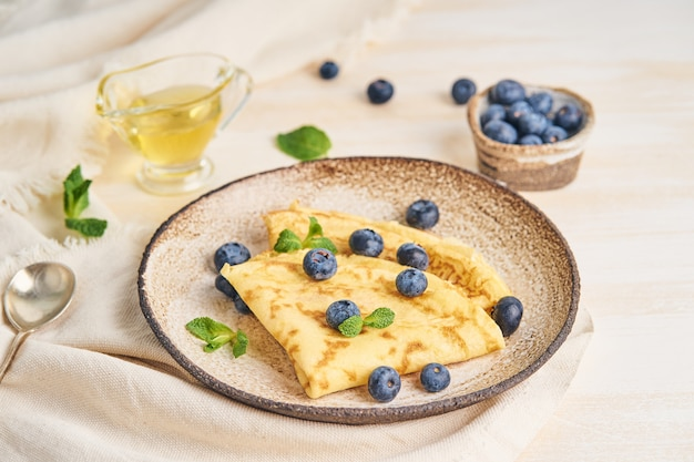 Zwei pfannkuchen mit blaubeeren und minze auf platte, seitenansicht