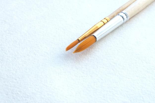 Zwei pinsel auf einem weißen blatt aquarellpapier