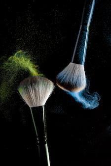 Zwei pinsel für make-up mit blauen make-upschatten in der bewegung auf einem schwarzen hintergrund.