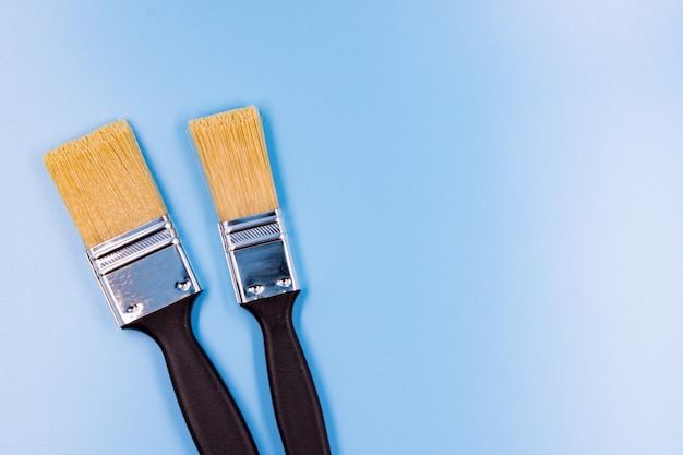 Zwei pinsel zum malen auf blauem hintergrund