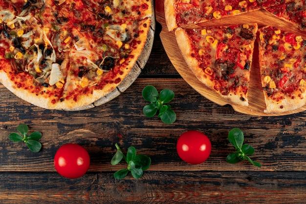 Zwei pizzen in einem pizzaboard mit tomaten und minzblättern nahaufnahme auf einem dunklen hölzernen hintergrund