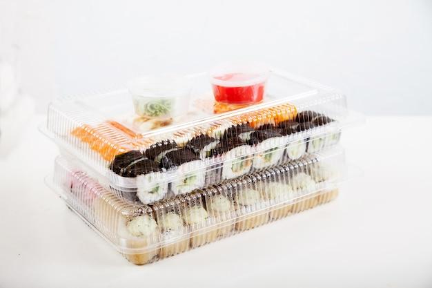 Zwei plastikboxen mit rollensätzen, wasabi und ingwer auf einem weißen teller.