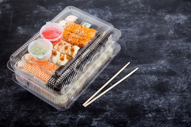 Zwei plastikboxen mit rollensets, wasabi und ingwer, bambusstäbchen auf schwarzem hintergrund.