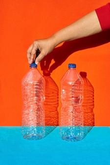 Zwei plastikflaschen mit einer hand, die eine davon hält