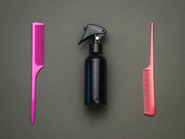 Zwei plastikkämme und ein haarspray auf schwarzem hintergrund. ein werkzeug für die haarpflege. flach liegen. Premium Fotos