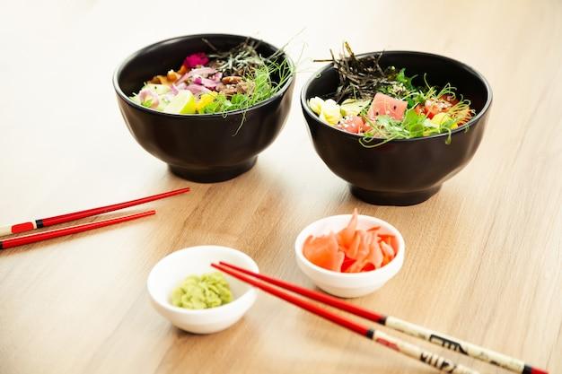 Zwei poke-salate mit rindfleisch und thunfisch in einer schüssel auf einem tisch im restaurant. poke salate in einer schüssel neben stäbchen und ingwer mit wasabi. asiatisches salatkonzept.
