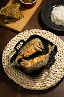 Zwei pommes frites makrelen auf eine schwarze pfanne legen