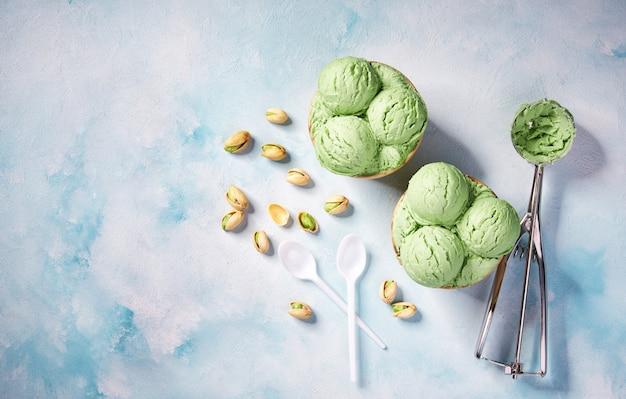 Zwei portionen pistazieneis in pappbecher auf minzfarbenhintergrund, draufsicht