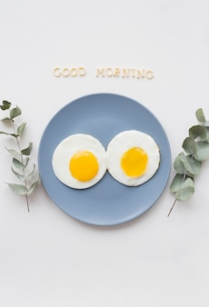 Zwei poschierte eier auf einem teller mit good morning