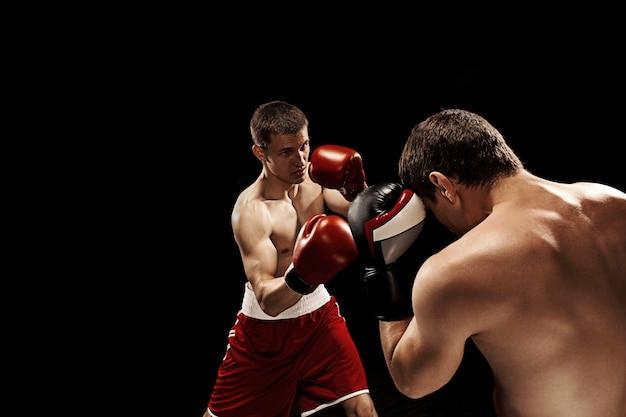 Zwei professionelle boxer, die an der schwarzen wand boxen