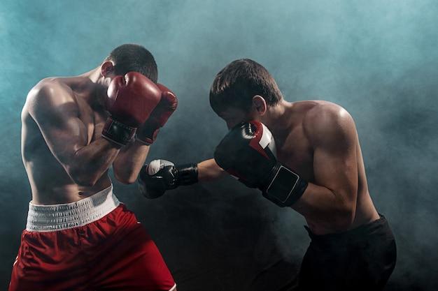 Zwei professionelle boxerboxen auf schwarzem rauch