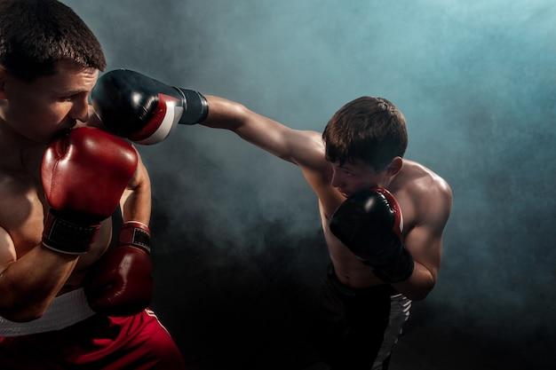 Zwei professionelle boxerboxen auf schwarzem rauch,