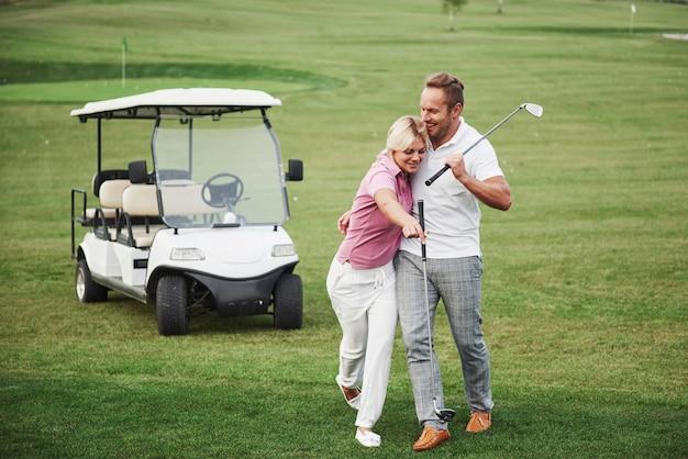 Zwei professionelle golfer, eine frau und ein mann, gehen zusammen zum nächsten loch. liebhaber umarmen und lächeln, sie haben ein date