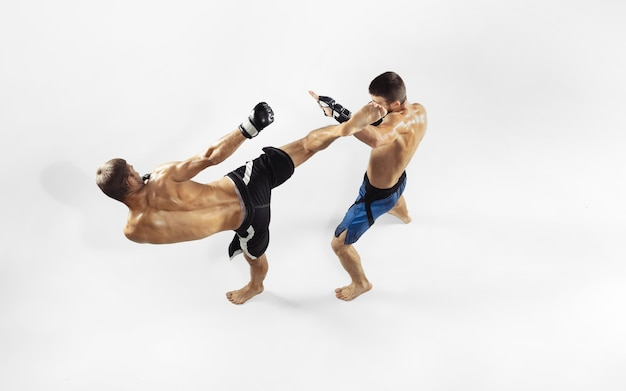 Zwei professionelle mma-kämpfer, die auf weißem studio isoliert boxen.