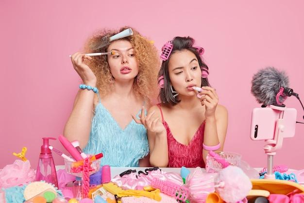 Zwei professionelle visagisten zeichnen ein tutorial über kosmetik auf, tragen lidschatten und lippenstift auf, verwenden verschiedene schönheitsprodukte, um die frisur vor der kamera zu posieren