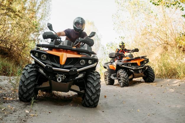 Zwei quadfahrer fahren im wald, vorderansicht