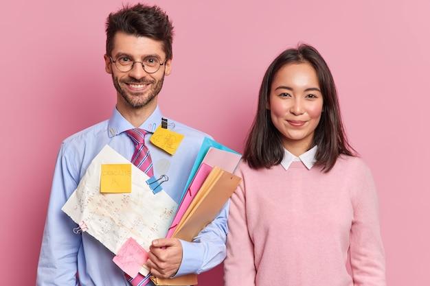 Zwei qualifizierte, vielfältige studentinnen und studenten stehen froh nebeneinander und bereiten gemeinsam ein wissenschaftliches projekt vor