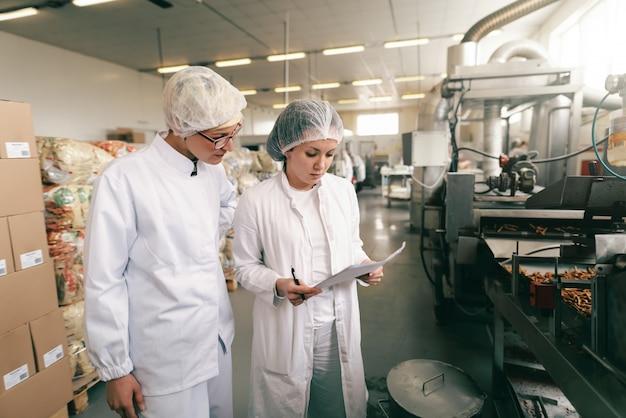 Zwei qualitätsprofis in weißen sterilen uniformen überprüfen die qualität der salzstangen, während sie in der lebensmittelfabrik stehen.