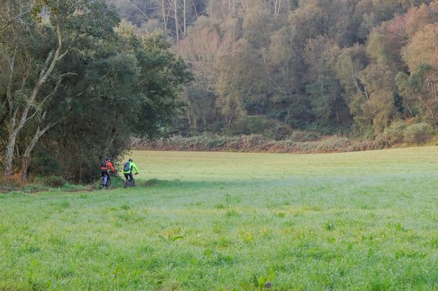 Zwei radfahrer trainieren auf dem berg zwischen grünen feldern