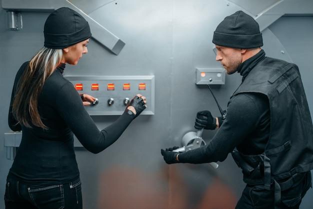 Zwei räuber in uniform versuchen, das tresorschloss zu öffnen