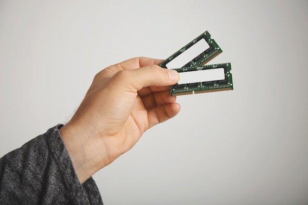 Zwei ram-chips in der hand eines mannes isoliert auf weiß