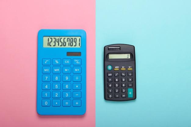 Zwei rechner auf rosa blauem pastellhintergrund. berechnung oder zählung. minimalismus. draufsicht