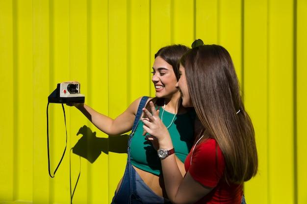 Zwei recht junge glückliche frauen, die foto mit retro- kamera machen und haben eine große zeit