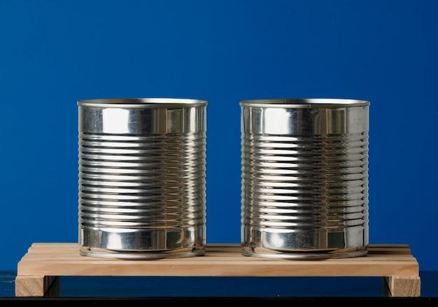 Zwei recycelte dosen auf holzbrettern mit blauem hintergrund