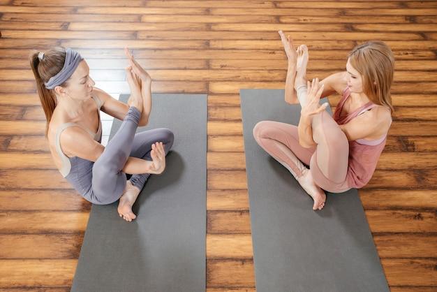 Zwei reife frauen, die sich auf matten im yogastudio-freundschafts- und sportkonzept dehnen