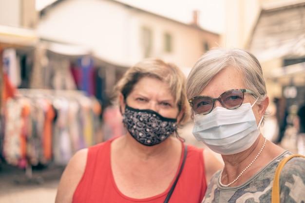 Zwei reife frauen mit gesichtsmasken, die auf dem markt im freien spazieren gehen