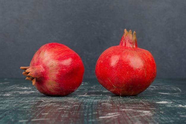 Zwei reife granatäpfel auf marmortisch.