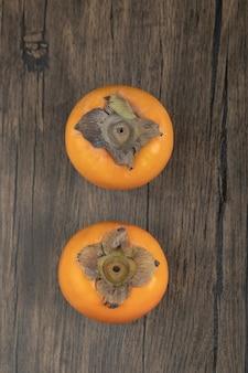 Zwei reife kakifrüchte auf holzoberfläche gelegt