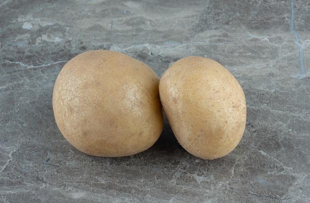 Zwei reife kartoffeln, auf dem marmortisch.