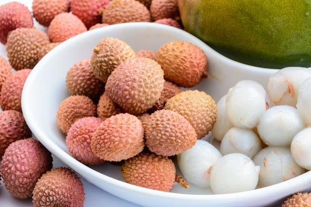 Zwei reife mangos, umgeben von reifen litschi-früchten auf einem teller auf weißem hintergrund. reife litschi ohne schale.