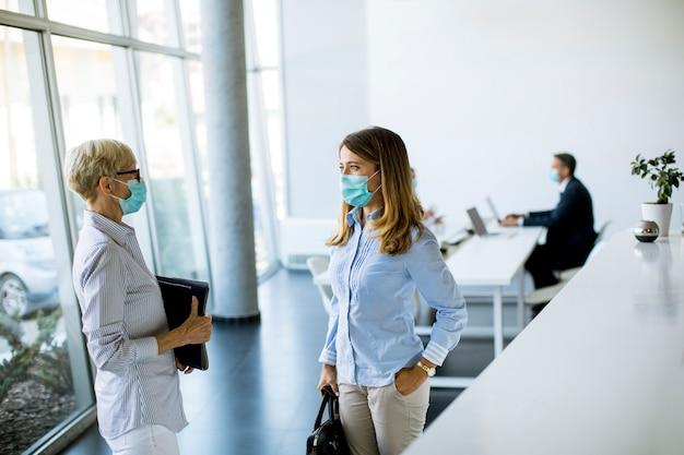 Zwei reife und junge geschäftsfrauen, die im büro sprechen und eine maske als virenschutz tragen