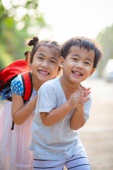 Zwei reizende asiatische kinderjungen und -mädchen mit scherzendem lächelndem gesicht