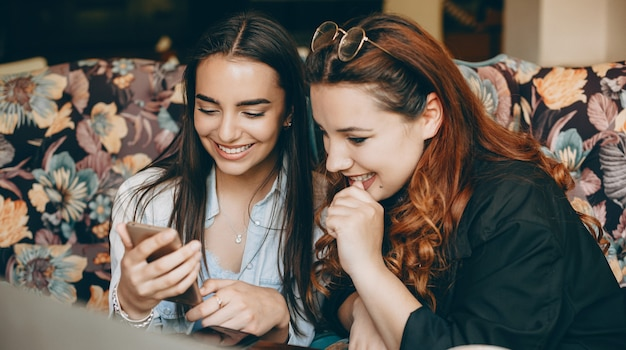 Zwei reizende junge frau, die einen smartphone-bildschirm lachend betrachtet, während sie in einem café sitzt.