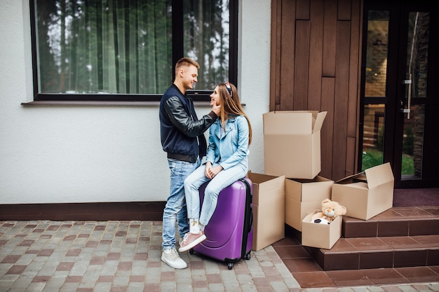 Zwei reizende person ziehen in neues haus, betreten ein neues zuhause, frau sitzen am koffer.