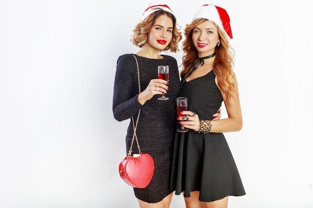 Zwei reizende sexy mädchen im roten weihnachtsmann-weihnachtsmann-feiertagshut, der aufwirft, hält glas wein.