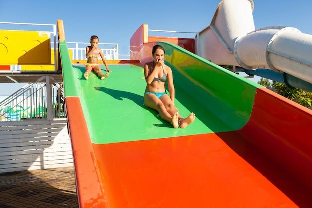 Zwei reizende süße lustige schwestern steigen von einer bunten hellen rutsche in einen pool mit klarem transparentem wasser ab und genießen die warme helle sonne