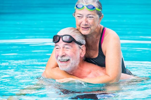 Zwei rentner oder reife alte leute, die sommer und urlaub im schwimmbad genießen, gemeinsam spaß beim lächeln und lachen haben - paar süße senioren verliebt - glücklicher lebensstil und gesundes konzept
