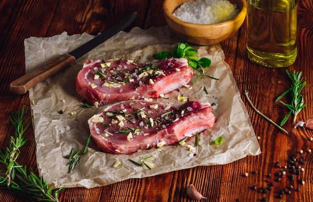 Zwei rib steaks mit gewürzen zum braten vorbereitet