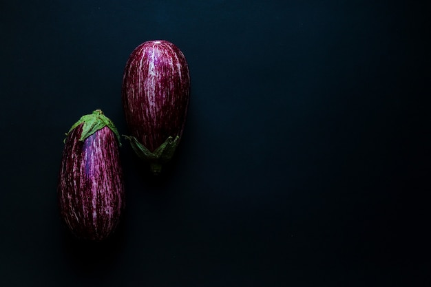 Zwei rohe auberginen auf dunklem hintergrund selektiver fokus nahaufnahme draufsicht erntekonzept