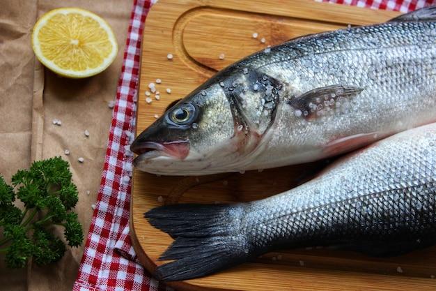 Zwei rohe fische auf einem schneidebrett verziert mit einer zitronenscheibe nahaufnahmetextur oder hintergrund