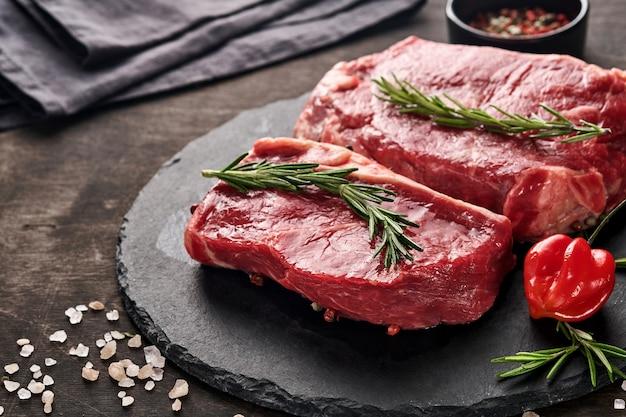 Zwei rohe new yorker steaks mit rosmarin und gewürzen auf einem stück pergamentpapier auf altem dunklem stein