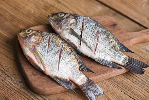 Zwei rohe nil-tilapia-süßwasserfische auf holzbrett - frischer tilapia-fisch zum kochen von lebensmitteln