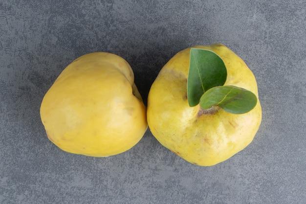 Zwei rohe quittenfrüchte isoliert auf einer grauen oberfläche